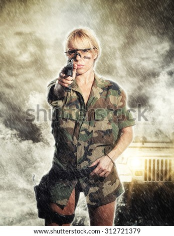 beautiful sexy girl holding gun under the storm - stock photo