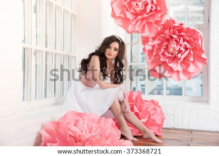 Beautiful sexy girl in a long dress with a huge pink flowers sitting by the window. - stock photo