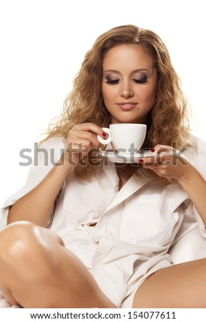 beautiful sexy girl in a white shirt enjoys her morning coffee - stock photo