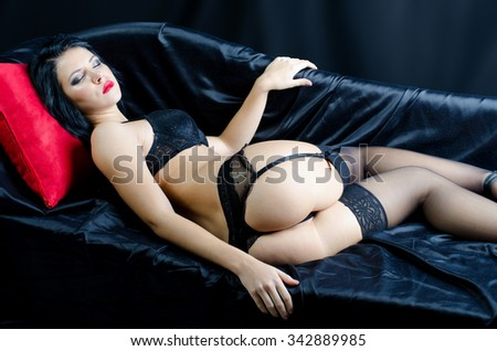 Beautiful sexy girl in black laced lingerie, garters and leggings lying on bed covered with black satin sheets and sleeping with head on red pillow. - stock photo