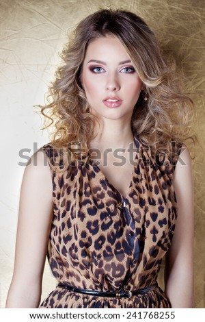beautiful sexy girl in leopard dress in bright makeup in the Studio on a gold background - stock photo