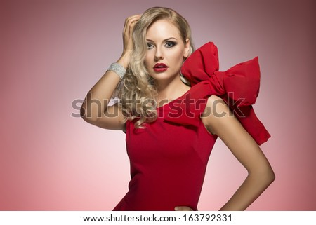 beautiful sexy girl in red with big bow on shoulder keeping a hand near the hair. looking expressive in camera - stock photo