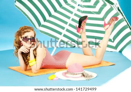 Beautiful sexy girl pin up in a bright bikini resting, tans on the beach under sun umbrella - stock photo