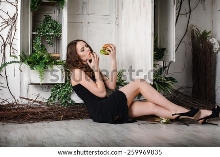 beautiful, sexy girl with a great burger. eats. Concept. weight loss. - stock photo