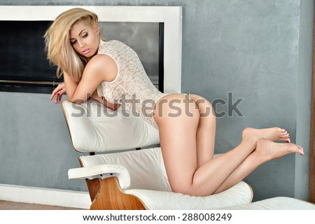 Beautiful sexy lady in elegant white bodysuit. Portrait of fashion model girl indoors. Beauty blonde woman with attractive buttocks in lace lingerie. Female ass in underwear. Naked body - stock photo
