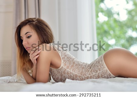 Beautiful sexy lady in elegant white bodysuit. Portrait of fashion model girl indoors. Beauty brunette woman with attractive buttocks in lace lingerie. Female ass in underwear. Naked body - stock photo