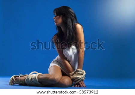 beautiful sexy lady tied with rope over blue background - stock photo