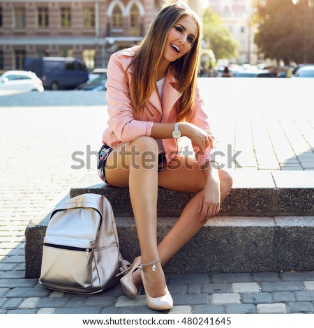 Beautiful   sexy lady  wearing fashionable clothes, handbag,  silver watches sunglasses sitting down in the city. Bright make up, tan body, long legs.