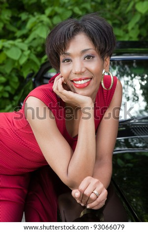 Beautiful sexy Latin woman with a 1970s style muscle car - stock photo