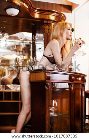 Beautiful sexy lingerie girl model drink wine from glass standing at home behind the bar