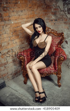 Beautiful sexy long hair woman posing in the camera. Studio shooting in interior. Model sitting in chair. Bright make up, red lips, black dress. Hot glamorous brunette woman. - stock photo