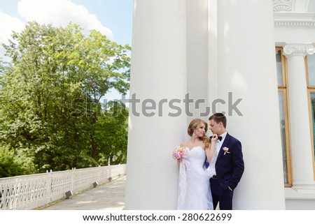 Beautiful sexy model girl in white dress. Wedding couple. Man in suit. Beauty blonde bride with brunette groom. Female and male portrait with bouquet. Woman with lace veil. Cute lady and guy outdoors - stock photo