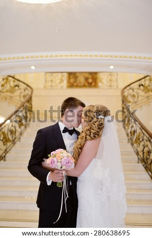 Beautiful sexy model girl in white dress. Wedding couple. Man in suit. Beauty blonde bride with brunette groom. Female and male portrait with bouquet. Woman with lace veil. Cute lady and guy indoors - stock photo