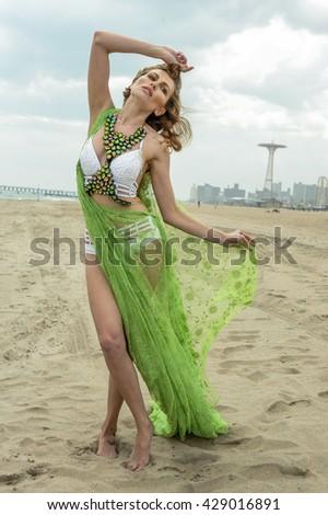 Beautiful sexy model in design bikini and cover up posing on the beach. - stock photo