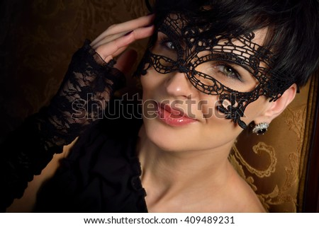 Beautiful, sexy mysterious woman - stranger in the lace mask with short black hair and playful eyes smiling, flirting in a wine cellar in the old castle