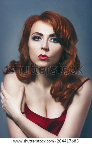 Beautiful sexy red-haired girl in a red dress with makeup and red lips