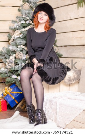 Beautiful sexy redhead girl in a New Year's interior