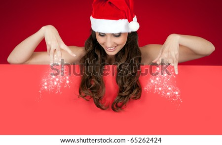 beautiful sexy santa woman sprinkling snow on board - stock photo