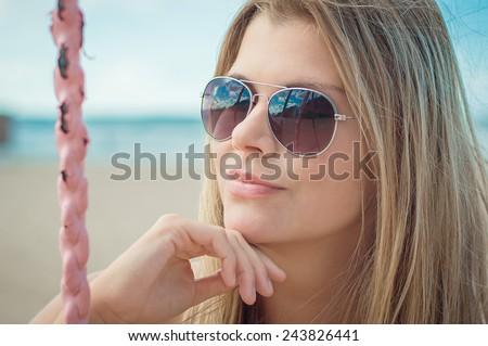 Beautiful sexy slim girl portrait. She is sunbathing on the beach on swing near sea waves - stock photo