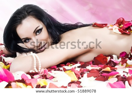 Beautiful sexy smiling woman with long black hair in rose petals - stock photo
