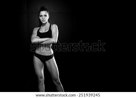 beautiful sexy sports girl on a dark background - stock photo