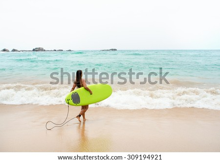 Beautiful sexy surfer girl on the beach. - stock photo