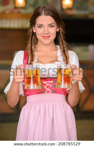 Beautiful, sexy waiter woman holding glasses of beer in a beer pub - stock photo
