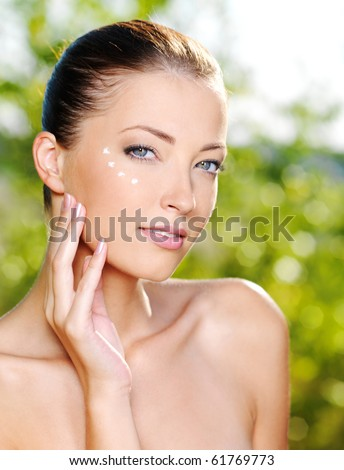 Beautiful sexy woman applying cosmetic cream on skin near eyes - Outdoors - stock photo