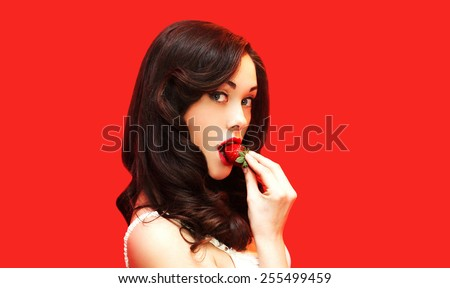 Beautiful sexy woman enjoying the taste of fresh strawberry on a red background