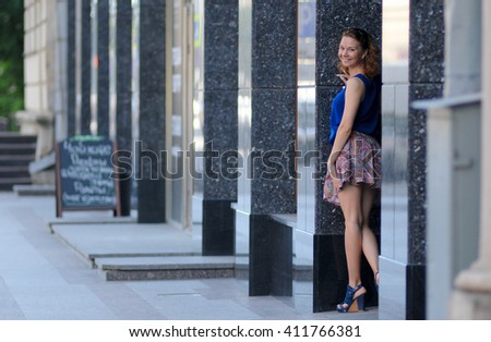 Beautiful sexy woman has mini skirt and blue blouse, high heeled shoes, wavy hair, legs and elegant body, stand on the street near building. Portrait urban city. Summer day. - stock photo