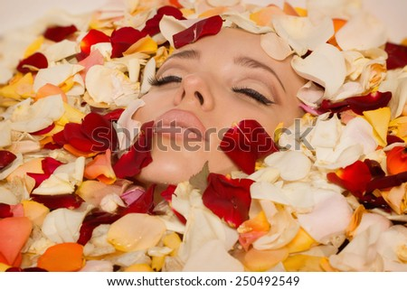 Beautiful sexy woman in bath with flowers petals. Spa body care. - stock photo