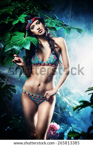 Beautiful sexy woman in bikini among tropical plants. Beauty, fashion. Spa, healthcare. Tropical vacation. - stock photo