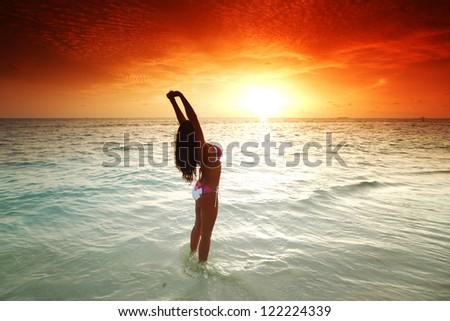 Beautiful sexy woman in bikini posing on beach - stock photo