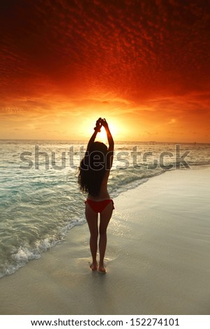 Beautiful sexy woman in bikini posing on beach - stock photo