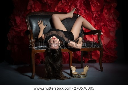 Beautiful sexy woman in black dress on a vintage couch posing against the backdrop of huge red roses - stock photo
