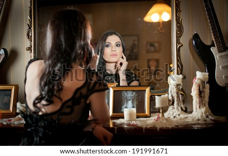 Beautiful sexy woman in black lace dress in vintage scenery with candles. Portrait of long hair brunette girl posing in luxury indoor. Attractive young fashionable female with creative makeup - stock photo