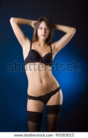 Beautiful sexy woman in black lingerie, on dark background - stock photo