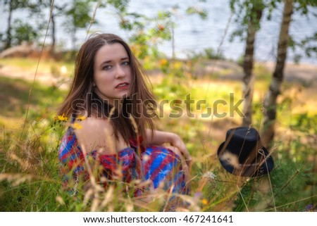 Beautiful sexy woman in felted striped dress in nomade style sitting near her black hat and turning around in summer field near river and trees