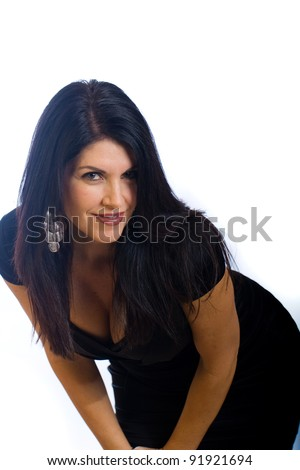 Beautiful, sexy woman in her 40s wearing a cute black cocktail dress. - stock photo