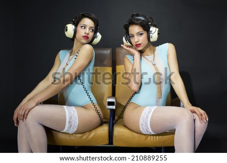 beautiful sexy woman in lingerie poses with another version of herself listening to music in a bar/lounge setting  - stock photo
