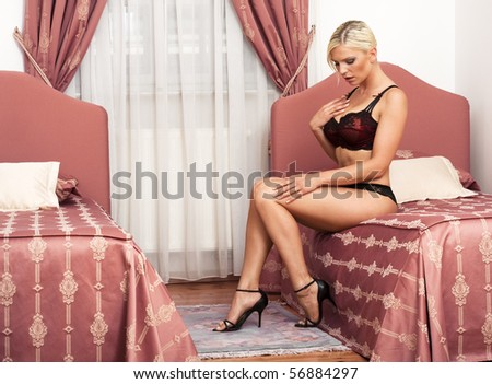 beautiful sexy woman in lingerie sitting on bed - stock photo