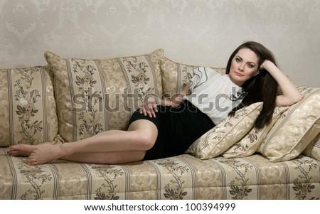 Beautiful sexy woman lying on sofa - stock photo