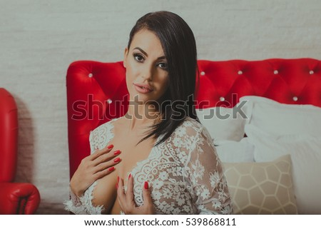 Beautiful sexy woman posing in a white lace dress in the bed