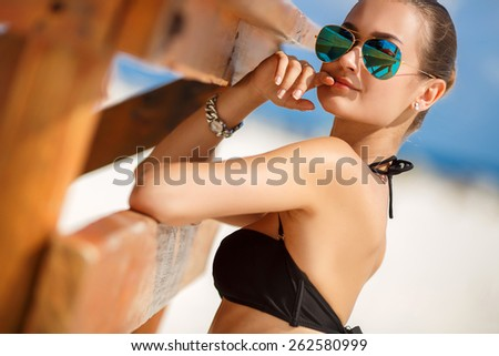 Beautiful sexy woman relaxing on the beach - outdoors. Young tanned woman on the beach in bikini and sunglasses. Young pretty hot sexy woman on the tropic island in summer near the sea - stock photo