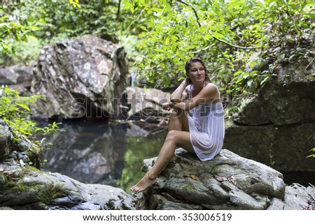 Beautiful sexy woman sits near the forest pond.