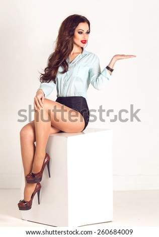 Beautiful sexy woman sitting on a white cube with space board and showing empty copy space for product on the open hand palm, on a bright background.  - stock photo