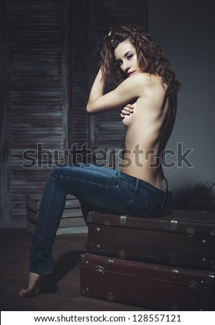 Beautiful sexy woman sitting on her suitcase in the room