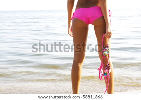 Beautiful sexy woman standing with back in water and holding top of her bikini - stock photo