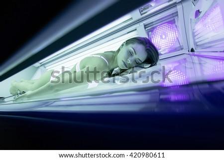 Beautiful sexy woman tanning in solarium - stock photo