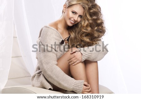 Beautiful sexy woman wearing bright sweater sitting on chair, looking at camera.